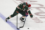 Minnesota Wild's Zach Parise controls the puck against Montreal Canadiens' Paul Byron in the first period of an NHL hockey game Sunday Oct. 20, 2019, in St. Paul, Minn. (AP Photo/Stacy Bengs)