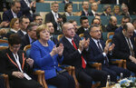 Turkey's President Recep Tayyip Erdogan, front centre, with Germany's Chancellor Angela Merkel, 2nd left, applaud during the opening ceremony of a Turkish-German university's new campus, in Istanbul, Friday, Jan. 24, 2020. Merkel is meeting Turkish President Recep Tayyip Erdogan in Istanbul on Friday for talks that are expected to focus on the future of a migration deal between Turkey and the EU that helped decrease refugee flows to Europe. (Presidential Press Service via AP, Pool)
