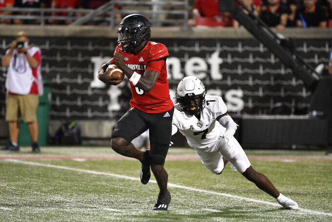 Louisville quarterback Malik Cunningham (3) runs from the grasp of Central Florida defensive back Davonte Brown (7) during the first half of an NCAA college football game in Louisville, Ky., Friday, Sept. 17, 2021. (AP Photo/Timothy D. Easley)