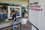 Shoppers wear protective face masks as they walk past a social distancing sign at the Ellenton Premium Outlet stores Friday, Nov. 27, 2020, in Ellenton, Fla. Attendance at the mall was down in an attempt to avoid spreading the corona virus. (AP Photo/Chris O'Meara)