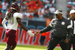 Bethune-Cookman head coach Terry Sims congratulates cornerback Trevor Merritt (20) after a play during the first half of an NCAA college football game against Miami, Saturday, Sept. 14, 2019, in Miami Gardens, Fla. (AP Photo/Wilfredo Lee)