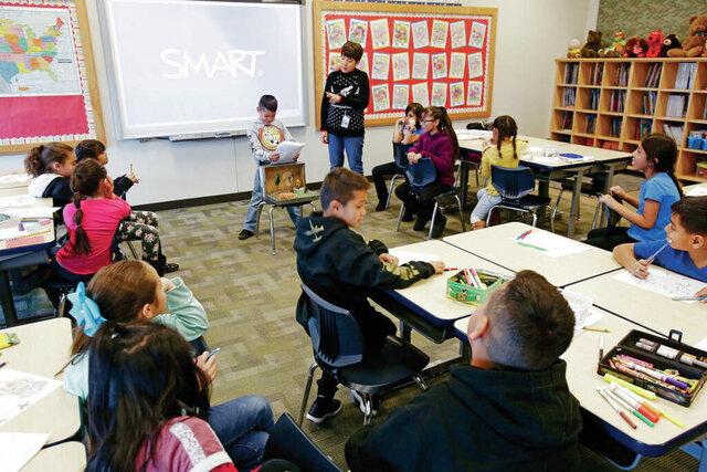 In this undated image, Alicia Ayala, a third grade dual-language teacher at El Camino Real Academy in Santa Fe, New Mexico, helps Ian Lopez Rascon, 8, give a report on lions. (Luis Sánchez Saturno/Santa Fe New Mexican via AP)