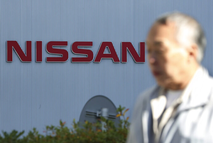In this Jan. 9, 2019, photo, a man walks past the logo at global headquarters of Nissan Motor Co., Ltd. in Yokohama, near Tokyo. Nissan has lowered its profit forecast for the fiscal year through March as the Japanese automaker, contends with slowing sales and the fallout from the loss of its former chairman, Carlos Ghosn. Nissan Motor Co. said Wednesday, April 24, 2019 it expects to post a 319 billion yen profit ($2.9 billion) for the fiscal year, marking a 22 percent drop from its earlier 410 billion yen ($3.7 billion) profit forecast earlier. (AP Photo/Koji Sasahara)