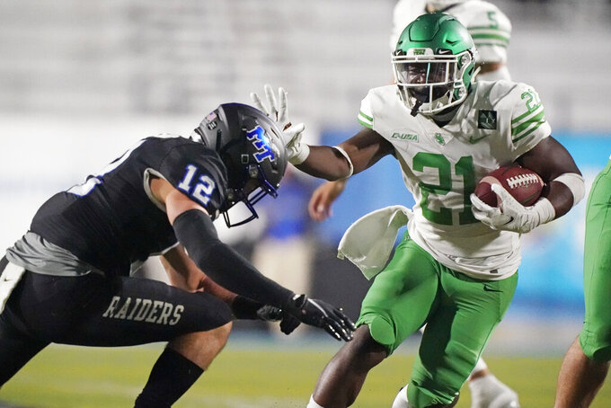 North Texas running back Nic Smith (21) tries to get past Middle Tennessee safety Reed Blankenship (12) in the second half of an NCAA college football game Saturday, Oct. 17, 2020, in Murfreesboro, Tenn. (AP Photo/Mark Humphrey)