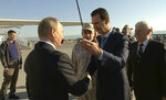 FILE - In this Monday, Dec. 11, 2017 file frame grab made available by Russian Presidential TV Syrian President Bashar Assad, right, greets Russian President Vladimir Putin upon his arrival to the Hemeimeem air base in Syria.  Assad has survived years of war and millions of dollars in money and weapons aimed at toppling him. Now after nearly eight years of conflict, he is poised to be readmitted to the fold of Arab nations, a feat once deemed unthinkable as he brutally crushed a years-long uprising against his family's rule.  (Presidential TV photo via AP, File)