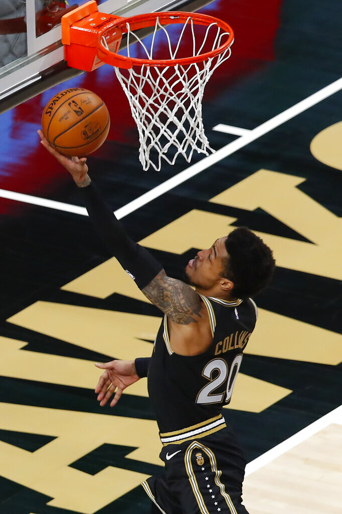 Atlanta Hawks forward John Collins (20) goes up for a shot in the first half of an NBA basketball game against the Minnesota Timberwolves on Monday, Jan. 18, 2021, in Atlanta. (AP Photo/Todd Kirkland)