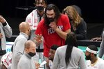 New Orleans Pelicans' Steven Adams, in red shirt, talks with members of the coaching staff during the first half of the team's NBA basketball game against the Dallas Mavericks in Dallas, Wednesday, May 12, 2021. Adams did not play in the game. (AP Photo/Tony Gutierrez)