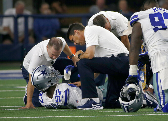 Dallas Cowboys defensive end Taco Charlton (97) is checked on by medical staff after suffering an unknown injury in the first half of a preseason NFL football game against the Houston Texans in Arlington, Texas, Saturday, Aug. 24, 2019. (AP Photo/Michael Ainsworth)