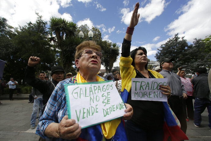 "A woman holds a sign with a message that reads in Spanish; ""Galapagos is not to be sold, but to be defended,"" during a protest against the government's plan to allow the U.S. military to use a Galapagos island for aircraft on anti-drug trafficking flights, outside the government palace in Quito, Ecuador, Monday, June 17, 2019. Protesters say the plan was a threat to the environment of the U.N. world heritage site as well as Ecuador's sovereignty. (AP Photo/Dolores Ochoa)"