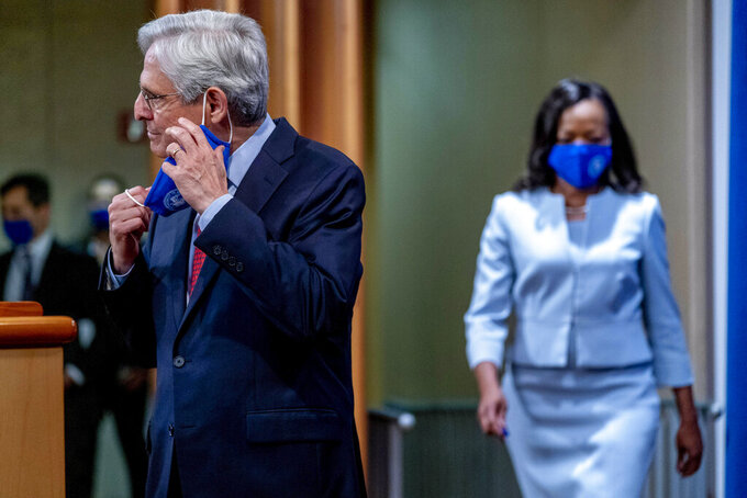 Attorney General Merrick Garland and Assistant Attorney General for Civil Rights Kristen Clarke, right, arrives for a news conference at the Department of Justice in Washington, Thursday, Aug. 5, 2021, to announce that the Department of Justice is opening an investigation into the city of Phoenix and the Phoenix Police Department. (AP Photo/Andrew Harnik)