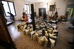 Volunteers try to save ancient music books by placing them to dry at the first floor of Venice Conservatory after recovering them from ground floor, Italy, Saturday, Nov. 16, 2019. High tidal waters returned to Venice on Saturday, four days after the city experienced its worst flooding in 50 years. Young Venetians are responding to the worst flood in their lifetimes by volunteering to help salvage manuscripts, clear out waterlogged books and lend a hand where needed throughout the stricken city.(AP Photo/Luca Bruno)