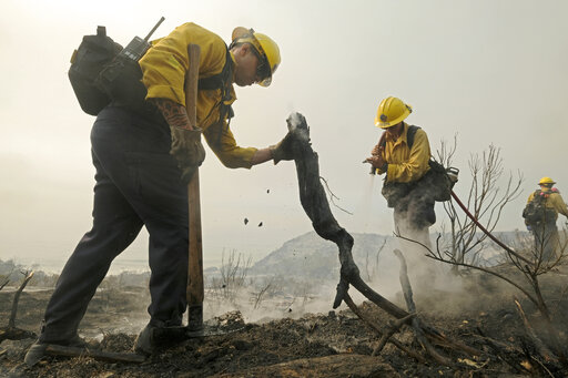 County of Santa Barbara Fire Department firefighters extinguish a roadside fire off the U.S. 101 highway Wednesday, Oct. 13, 2021, in Goleta, Calif. A wildfire raging through Southern California coastal mountains threatened ranches and rural homes and kept a major highway shut down Wednesday as the fire-scarred state faced a new round of dry winds that raise risk of flames. (AP Photo/Ringo H.W. Chiu)