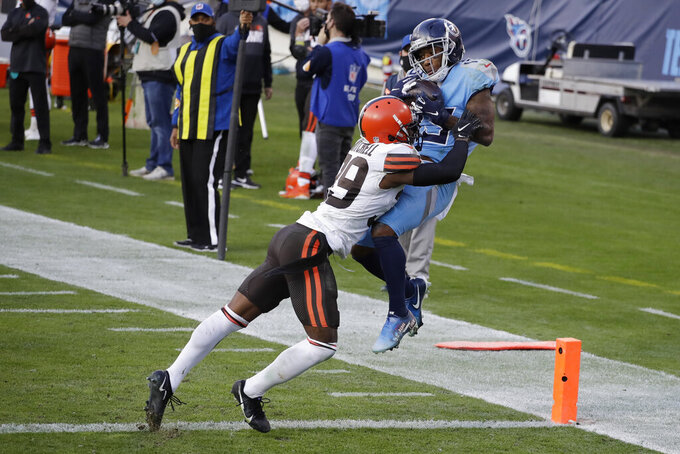 Tennessee Titans wide receiver Cameron Batson (13) catches a touchdown pass as he is hit by Cleveland Browns cornerback Terrance Mitchell (39) in the second half of an NFL football game Sunday, Dec. 6, 2020, in Nashville, Tenn. (AP Photo/Ben Margot)