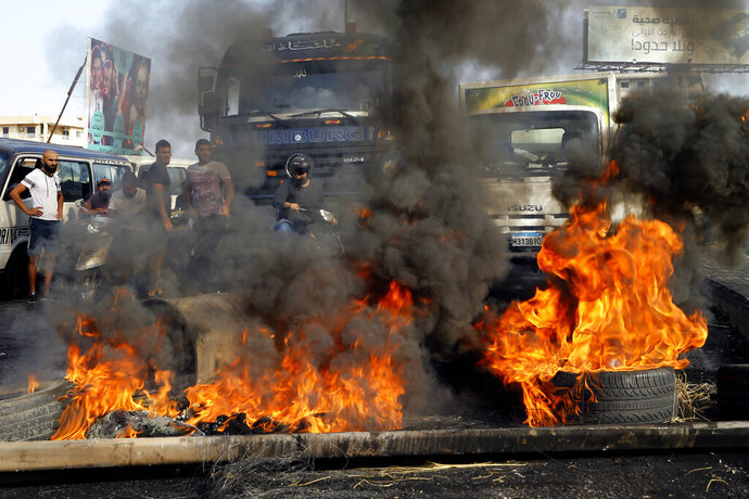 People queue on their cars as they try to cross a highway blocked by anti-government protesters by burning tires, during ongoing protests against the government, in Khaldeh, south of Beirut, Lebanon, Thursday, Nov. 14, 2019. Protesters have been holding demonstrations since Oct. 17 demanding an end to widespread corruption and mismanagement by the political class that has ruled the country for three decades. (AP Photo/Bilal Hussein)