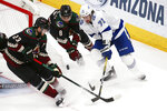 Tampa Bay Lightning center Anthony Cirelli (71) works against Arizona Coyotes defenseman Oliver Ekman-Larsson (23) and center Nick Schmaltz (8) for the puck during the second period of an NHL hockey game Saturday, Feb. 22, 2020, in Glendale, Ariz. (AP Photo/Ross D. Franklin)