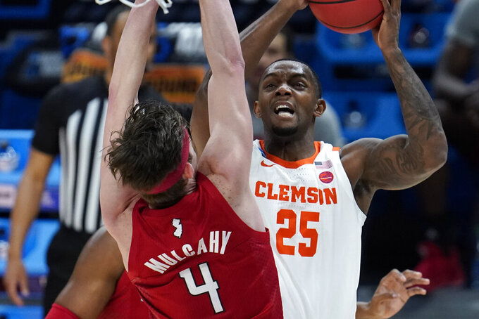 Clemson forward Aamir Simms (25) drives on Rutgers guard Paul Mulcahy (4) during the first half of a men's college basketball game in the first round of the NCAA tournament at Bankers Life Fieldhouse in Indianapolis, Friday, March 19, 2021. (AP Photo/Paul Sancya)