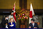 British International Trade Secretary Liz Truss, second left, signs a document with Japanese Foreign Minister Toshimitsu Motegi, right, for economic partnership between Japan and Britain at Iikura Annex of the Foreign Ministry in Tokyo Friday, Oct. 23, 2020. Japan and Britain signed a bilateral free trade deal Friday in the the first such major post-Brexit deal, reducing tariffs on Yorkshire lamb sold in Japan, as well as auto parts for Japan's Nissan plant. (Kimimasa Mayama/Pool Photo via AP)