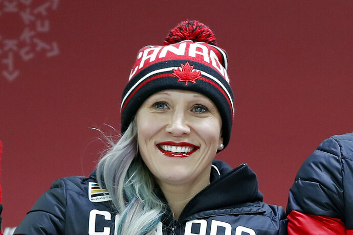 FILE - In this Feb. 21, 2018, file photo, Kaillie Humphries celebrates winning the bronze medal, with teammate Phylicia George (not shown), after the women's two-man bobsled final at the 2018 Winter Olympics in Pyeongchang, South Korea. Humphries _ one of the best pilots in the history of her sport _ has traded her red and white Canadian gear for red, white and blue U.S. apparel. No longer racing for her homeland of Canada, Humphries is now officially a member of USA Bobsled's national team after a nearly two-year saga that saw her not only claim that she was verbally and mentally abused by a Canadian coach to the point where she no longer felt safe but that her now-former national team simply discarded her.  (AP Photo/Andy Wong, File)