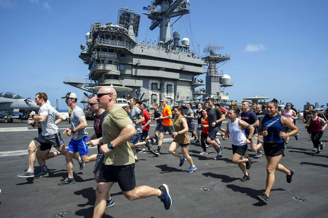 In this May 24, 2020, photo, provided by the U.S. Navy Sailors run on the flight deck aboard the aircraft carrier USS Dwight D. Eisenhower (CVN 69). When coronavirus made U.S. Navy ship stops in foreign countries too risky, the USS Dwight D Eisenhower and the USS San Jacinto were ordered to keep moving, and avoid all port visits. More than five months after they set sail, they have broken a record they never planned to achieve. As they steamed through the North Arabian Sea on June 25, they notched their 161st consecutive day at sea, breaking the previous Navy record of 160 days.  (Mass Communication Specialist 3rd Class Sophie A. Pinkham/U.S. Navy via AP)