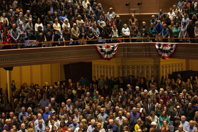 The crowd stands as the colors are presented to open the one-year commemoration of the Tree of Life synagogue attack at Soldiers & Sailors Memorial Hall and Museum, Sunday, Oct. 27, 2019, in Pittsburgh. A year ago, a gunman entered the Tree of Life synagogue and killed 11 members of three congregations, Dor Hadash, New Light and Tree of Life/Or L'Simcha, holding Shabbat services in the building. (AP Photo/Rebecca Droke)