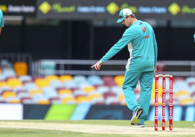 FILE - In this Jan. 19, 2021, fie photo, Australia's Steve Smith inspects the pitch ahead of play on the final day of the fourth cricket test between India and Australia at the Gabba, Brisbane, Australia. Steve Smith will miss Australia's limited-overs cricket tours to the West Indies and Bangladesh because of an elbow injury while David Warner and Pat Cummins are among the six players who've declared themselves unavailable. (AP Photo/Tertius Pickard, File)