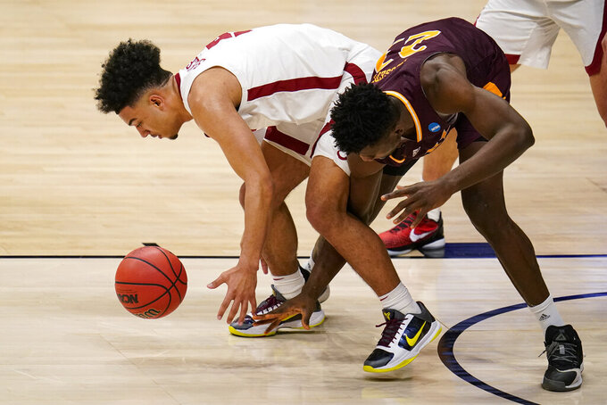 Alabama guard Jaden Shackelford (5) grabs a loose ball in front of Iona forward Nelly Junior Joseph (23) in the second half of a first-round game in the NCAA men's college basketball tournament at Hinkle Fieldhouse in Indianapolis, Saturday, March 20, 2021. (AP Photo/Michael Conroy)