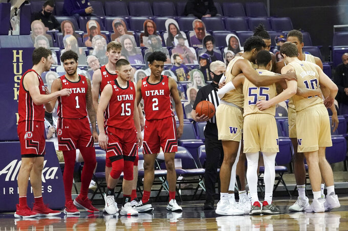 Washington players huddle at right as Utah players look on during the second half of an NCAA college basketball game, Sunday, Jan. 24, 2021, in Seattle. Washington won 83-79. (AP Photo/Ted S. Warren)