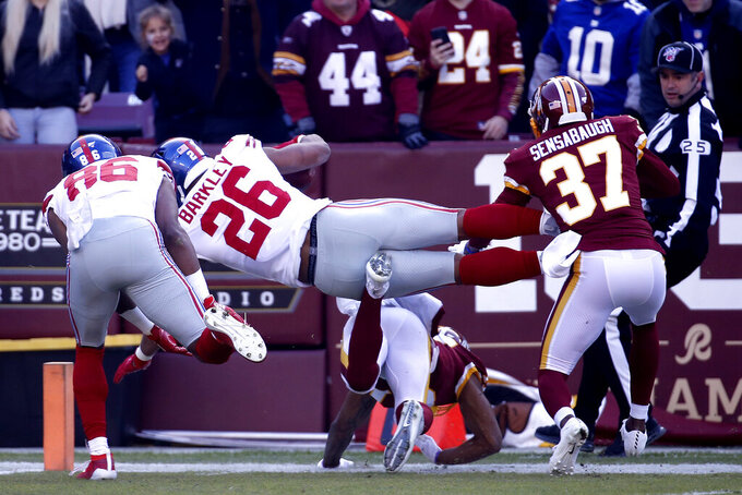 New York Giants running back Saquon Barkley (26) dives over Washington Redskins cornerback Aaron Colvin for a touchdown ona long run during the first half of an NFL football game, Sunday, Dec. 22, 2019, in Landover, Md. (AP Photo/Alex Brandon)