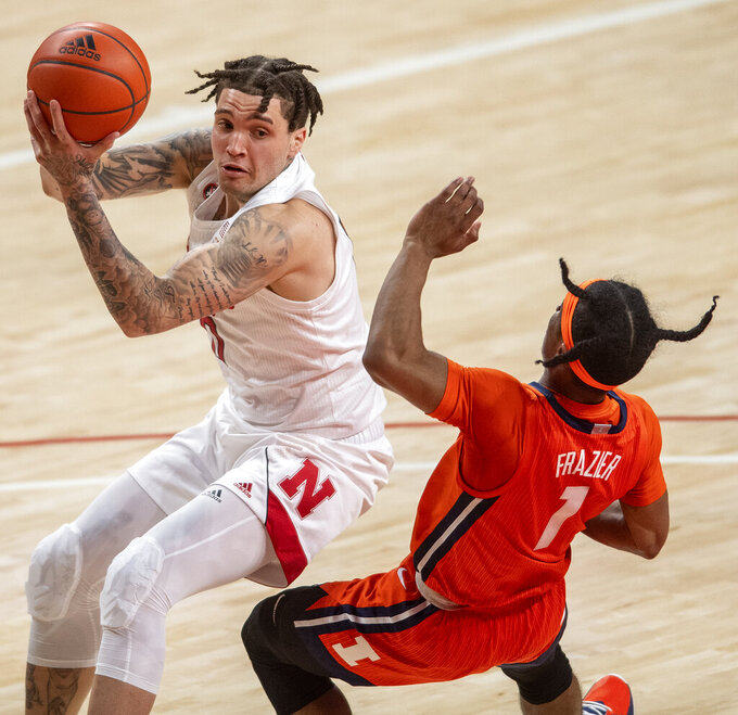 Nebraska guard Teddy Allen (0) knocks over Illinois' Trent Frazier (1) as he drives to the basket during the first half of an NCAA college basketball game on Friday, Feb. 12, 2021, in Lincoln, Neb.  (Francis Gardler/Lincoln Journal Star via AP)