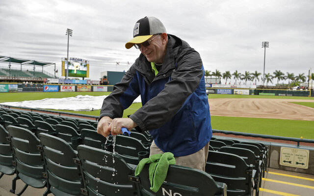 """FILE - In this March 19, 2019, file photo, Chuck Speer wrings out a rag after drying seats off at LECOM Park before a spring training baseball game between the Pittsburgh Pirates and the Detroit Tigers in Bradenton, Fla. The Pittsburgh Pirates have given their spring training home a deep clean as a proactive measure after a man in Manatee County tested positive for coronavirus. Pirates spokesman Brian Warecki said workers sanitized the clubhouse, press box, concession stands and other areas of LECOM Park in an """"overabundance of caution."""" LECOM Park is located in downtown Bradenton, which is in the middle of Manatee County. The cleaning was done on Tuesday, March 3, 2020, a scheduled day off for the Pirates. (AP Photo/Chris O'Meara, File)"""