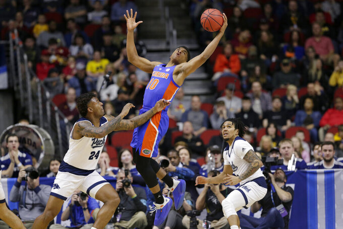 Florida's Noah Locke (10) leaps for a deflected ball over Nevada's Jordan Caroline (24) and Jazz Johnson, right, during the first half of a first round men's college basketball game in the NCAA Tournament in Des Moines, Iowa, Thursday, March 21, 2019. (AP Photo/Nati Harnik)