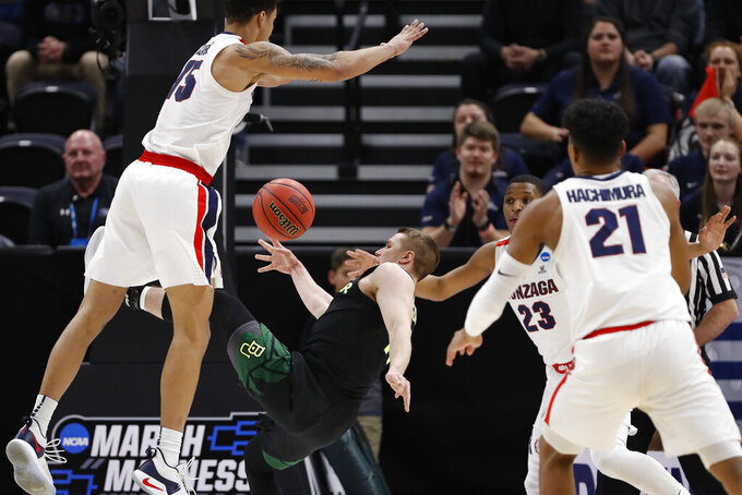Baylor guard Makai Mason stumbles while driving against Gonzaga forward Brandon Clarke, left and guard Zach Norvell Jr. (23) during the first half of a second-round game in the NCAA men's college basketball tournament Saturday, March 23, 2019, in Salt Lake City. (AP Photo/Jeff Swinger)