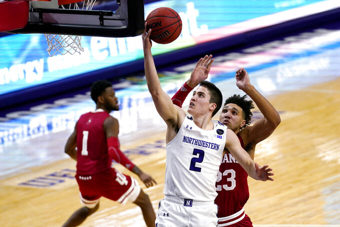 Northwestern guard Ryan Greer (2) drives to the basket past Indiana forward Trayce Jackson-Davis, right, during the second half of an NCAA college basketball game in Evanston, Ill., Wednesday, Feb. 10, 2021. (AP Photo/Nam Y. Huh)
