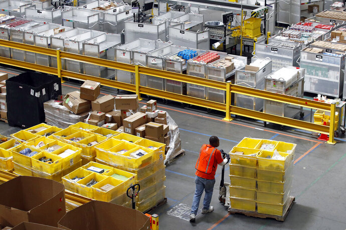 FILE - In this Aug. 3, 2017, file photo, a worker pushes bins at an Amazon fulfillment center in Baltimore. Amazon will spend more than $700 million to provide additional training to about one-third of its U.S. workforce. (AP Photo/Patrick Semansky, File)