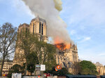 Notre Dame cathedral is burning in Paris, Monday, April 15, 2019. Massive plumes of yellow brown smoke is filling the air above Notre Dame Cathedral and ash is falling on tourists and others around the island that marks the center of Paris. (AP Photo)