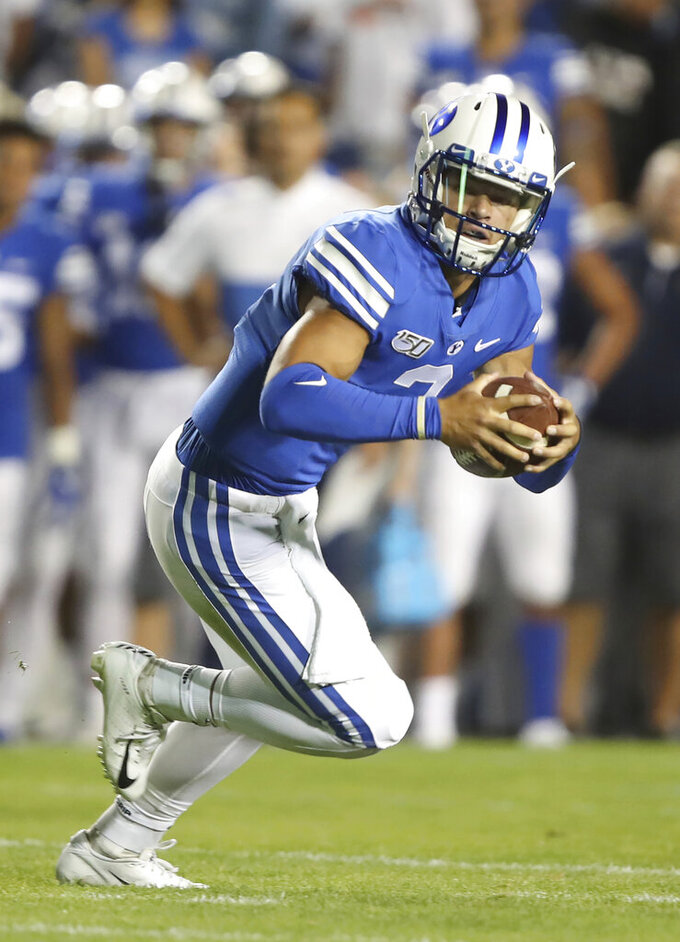FILE - In this Thursday, Aug. 29, 2019, file photo, BYU quarterback Jaren Hall rolls out in the first half during an NCAA college football game against Utah in Provo, Utah. The BYU quarterback who steps in for Zach Wilson this season may just be from out of left field. That's only because Jaren Hall did play some outfield on the Cougars baseball team.(AP Photo/George Frey, File)
