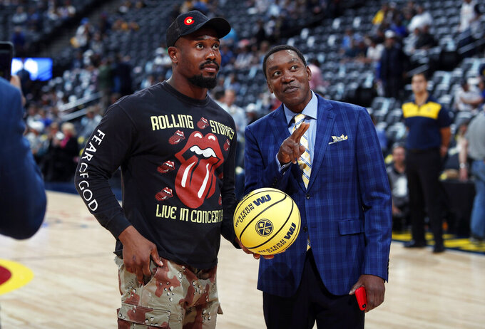 Denver Broncos linebacker Von Miller, left, gets tips on how to shoot the ceremonial first shot from television analyst Isaiah Thomas before the first half of Game 5 of an NBA basketball first-round playoff series between the San Antonio Spurs and Denver Nuggets, Tuesday, April 23, 2019, in Denver. (AP Photo/David Zalubowski)