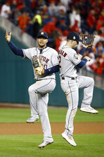 Houston Astros first baseman Yuli Gurriel, left, and third baseman Alex Bregman celebrate after their teams win against the Washington Nationals in Game 4 of the baseball World Series Saturday, Oct. 26, 2019, in Washington. The Astros won 8-1 to tie the series 2-2. (AP Photo/Patrick Semansky)