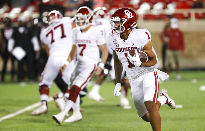 Oklahoma running back Seth McGowan carries during the first half of the team's NCAA college football game against Texas Tech, Saturday, Oct. 31, 2020, in Lubbock, Texas. (AP Photo/Mark Rogers)