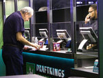 In this Oct. 8, 2019 photo, a customer makes a sports bet at the DraftKings sports book at Resorts Casino in Atlantic City, N.J. On Tuesday, March 30, 2021, DraftKings acquired the video production and distribution company Vegas Sports Information Network to add content to DraftKings' operations in 14 states. (AP Photo/Wayne Parry)