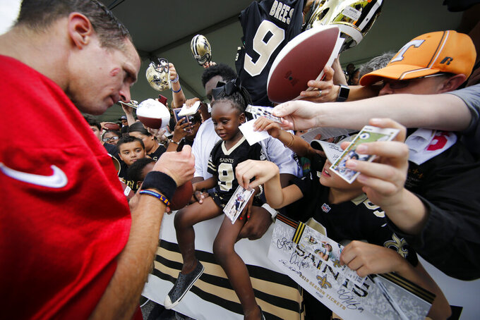 New Orleans Saints quarterback Drew Brees signs an autograph for Hailey Smith. 3, during training camp at their NFL football training facility in Metairie, La., Friday, July 26, 2019. (AP Photo/Gerald Herbert)