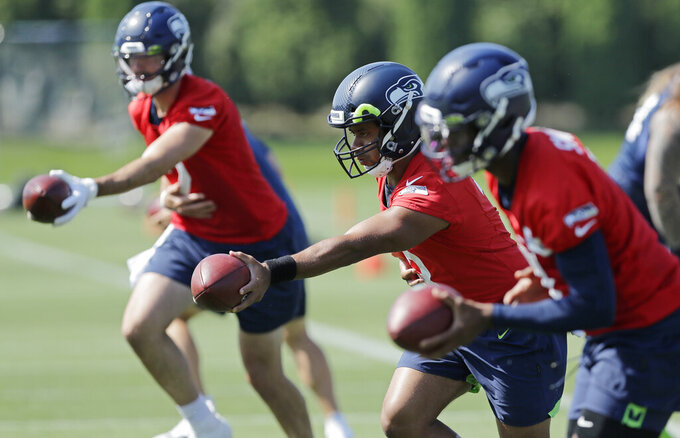 Seattle Seahawks quarterback Russell Wilson, center, drops back next to passes next to backup quarterbacks Paxton Lynch, left, and Geno Smith, right, during NFL football training camp, Monday, Aug. 5, 2019, in Renton, Wash. (AP Photo/Ted S. Warren)