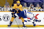 Nashville Predators center Yakov Trenin (13) tries to stop Tampa Bay Lightning right wing Barclay Goodrow (19) from getting to the puck during the first period of an NHL hockey game Tuesday, April 13, 2021, in Nashville, Tenn. (AP Photo/Mark Zaleski)