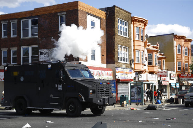 FILE - In this May 31, 2020 file photo, police deploy tear gas to disperse a crowd during a protest in Philadelphia over the death of George Floyd. Floyd died May 25 after he was pinned at the neck by a Minneapolis police officer.  Three class-action lawsuits filed in Philadelphia on Tuesday, July 14,  accuse the city of using military-level force against peaceful demonstrators protesting racial inequality and police brutality.   (AP Photo/Matt Rourke, File)