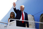 In this Aug. 7, 2019, photo, President Donald Trump and first lady Melania Trump board Air Force One for a trip to Dayton, Ohio and El Paso, Texas, at Andrews Air Force Base, Md. As Trump prepares to leave Friday for his annual August holiday at his lush New Jersey golf club, the president will confront a storm of crises, at home and abroad, that could set the course for his upcoming re-election bid. (AP Photo/Evan Vucci)