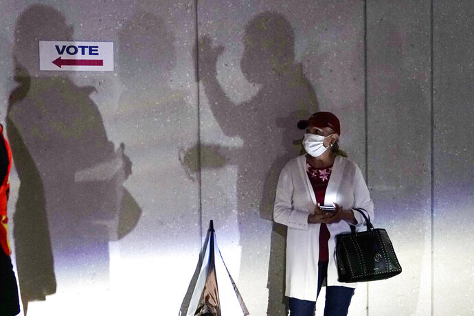 FILE - In this Oct. 19, 2020, file photo a woman waits to vote in Miami. Election officials are on high alert amid fears that U.S. polling stations could attract the same strain of partisan violence and civil unrest that erupted on American streets this year. (AP Photo/Lynne Sladky, File)