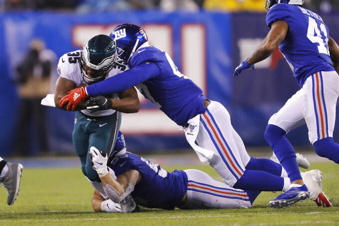 Philadelphia Eagles running back Boston Scott (35) is stopped by New York Giants outside linebacker Alec Ogletree (47) and New York Giants outside linebacker David Mayo (55) in the first half of an NFL football game, Sunday, Dec. 29, 2019, in East Rutherford, N.J. (AP Photo/Adam Hunger)