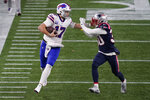 Buffalo Bills quarterback Josh Allen, left, gives a stiff arm to New England Patriots cornerback Jason McCourty in the first half of an NFL football game, Monday, Dec. 28, 2020, in Foxborough, Mass. (AP Photo/Charles Krupa)
