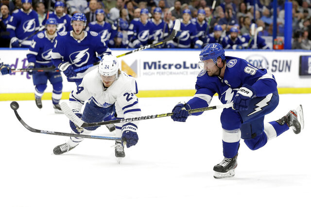 Tampa Bay Lightning center Steven Stamkos (91)gets off a shot in front of Toronto Maple Leafs right wing Kasperi Kapanen (24) during the second period of an NHL hockey game Tuesday, Feb. 25, 2020, in Tampa, Fla. (AP Photo/Chris O'Meara)