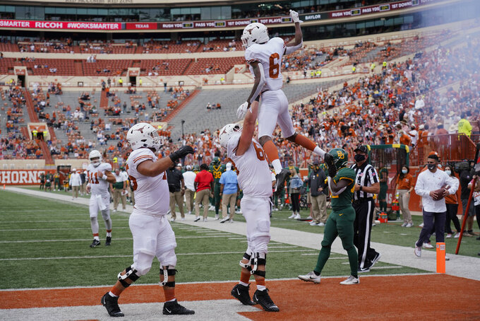 Texas' Joshua Moore (6) celebrates his touchdown catch with teammates against Baylor during the first half of an NCAA college football game in Austin, Texas, Saturday, Oct. 24, 2020. (AP Photo/Chuck Burton)